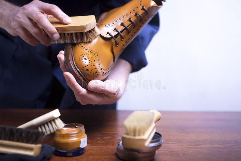 Le processus des chaussures de nettoyage Un homme nettoie ses chaussures photos stock