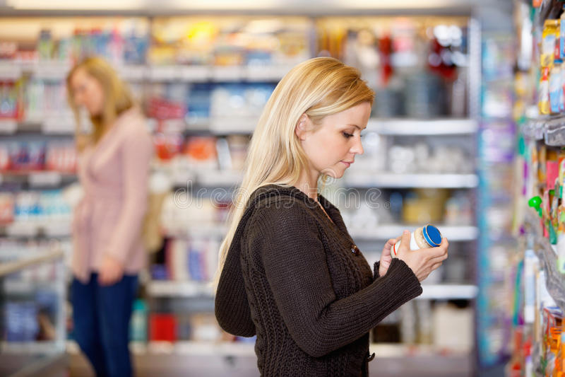 Le produit de jeune femme comparent image stock