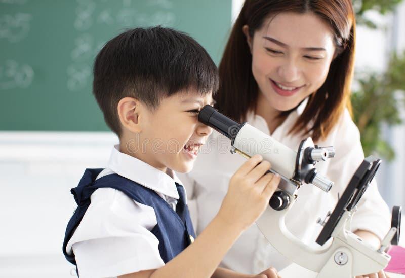 Le professeur aide l'enfant à entreprendre l'expérience avec le microscope image libre de droits
