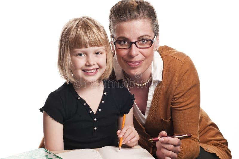 Le professeur aide la jeune écolière photographie stock libre de droits