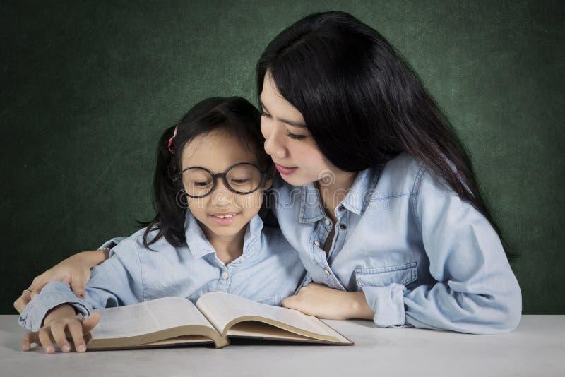 Le professeur aide son étudiant à lire un livre photographie stock