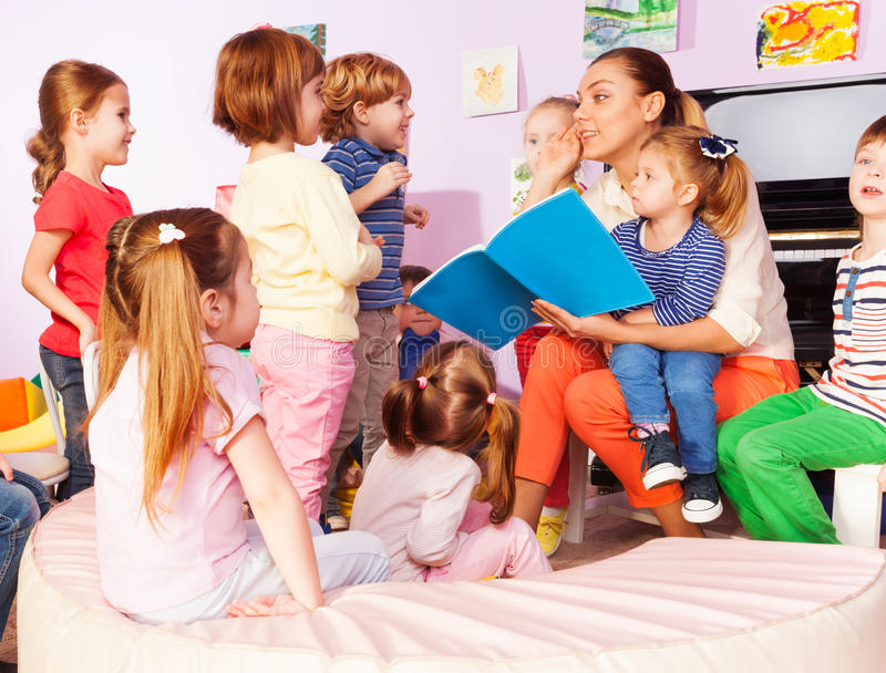 Le professeur avec des enfants a lu et discute le livre photo libre de droits