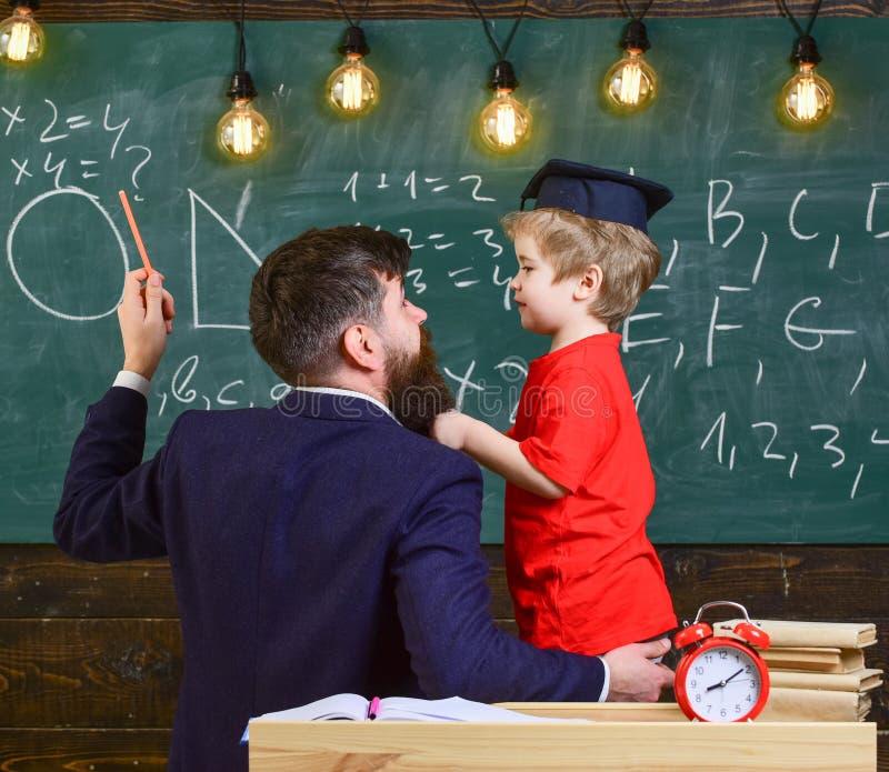 Le professeur avec la barbe, père enseigne le petit fils dans la salle de classe, tableau sur le fond Concept instructif de conve images libres de droits
