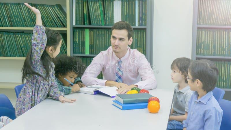 Le professeur caucasien souriant et le groupement de l'Asiatique badine l'étudiant lear images libres de droits