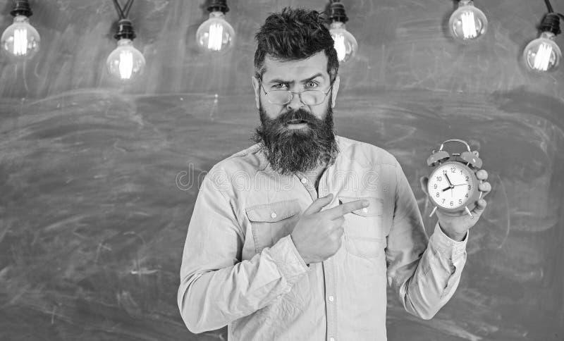 Le professeur dans des lunettes tient le réveil Concept de retard Homme avec la barbe et moustache sur le visage strict se dirige photographie stock libre de droits