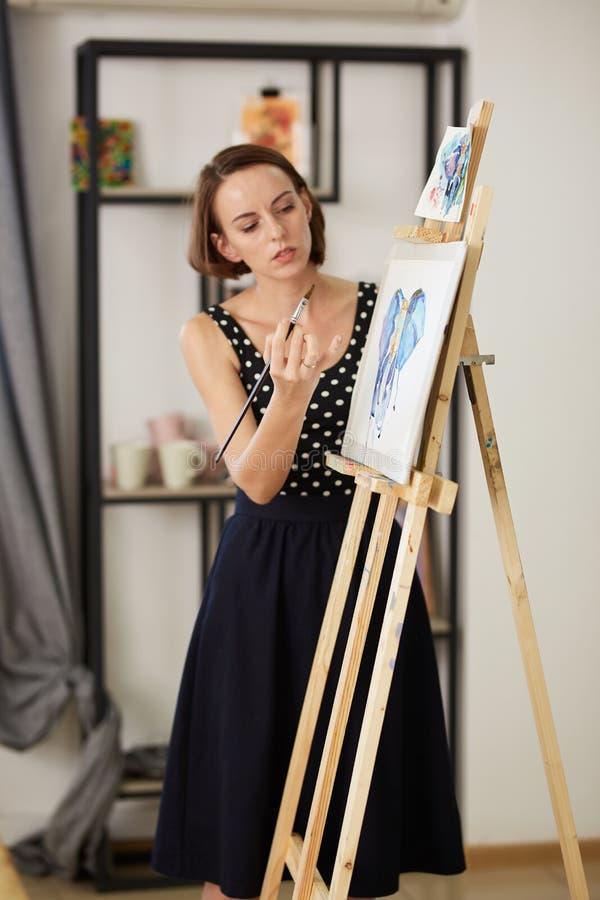 Le professeur de dessin de charme dans la belle robe montre la technique de dessin au chevalet dans le studio d'art images stock