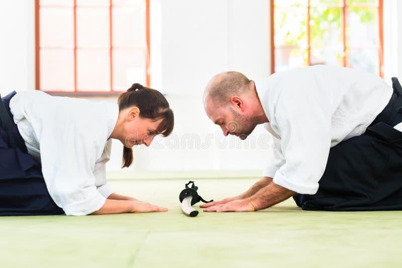 Le professeur et l'étudiant d'arts martiaux d'Aikido prennent un arc photos stock