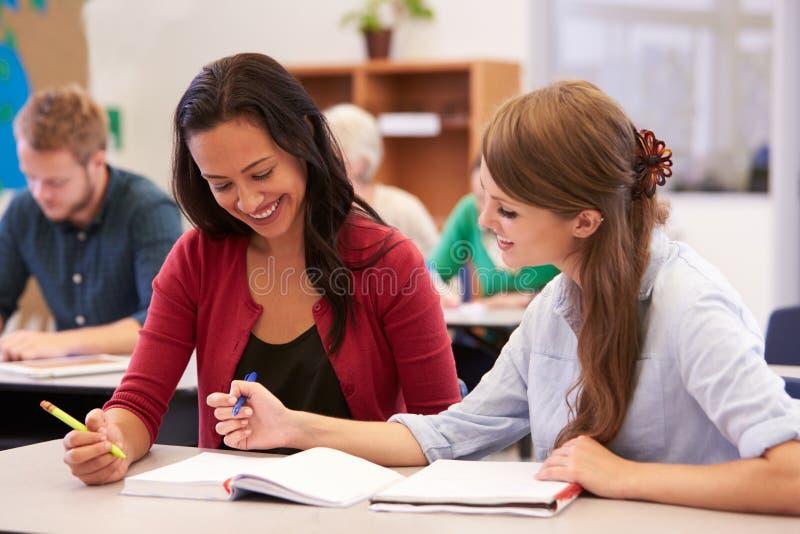 Le professeur et l'étudiant travaillent ensemble à la classe d'éducation des adultes photographie stock