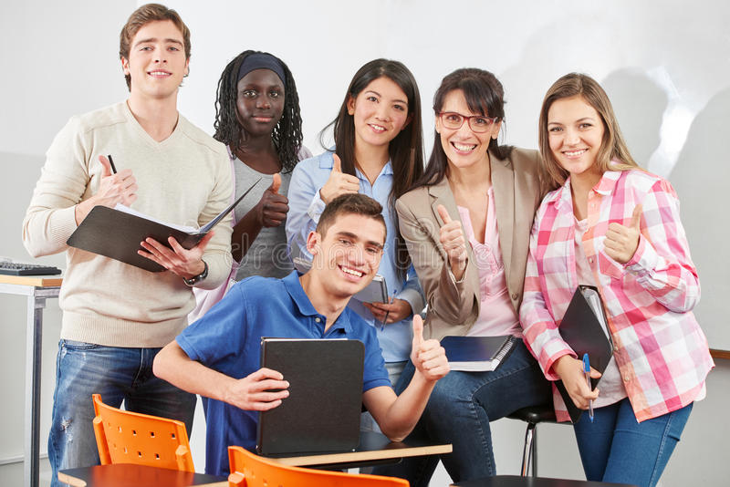 Le professeur et les étudiants tiennent leurs pouces  image libre de droits