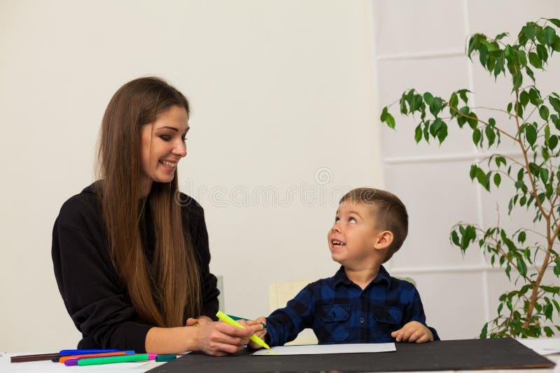 Le professeur féminin enseigne un petit garçon à dessiner à la table images stock