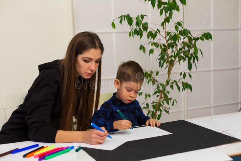 Le professeur féminin enseigne un petit garçon à dessiner à la table images libres de droits