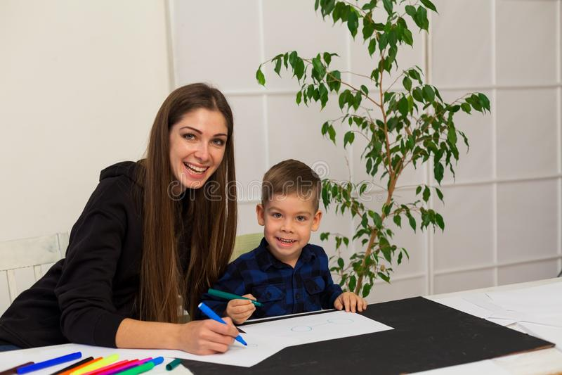 Le professeur féminin enseigne un petit garçon à dessiner à la table photo libre de droits