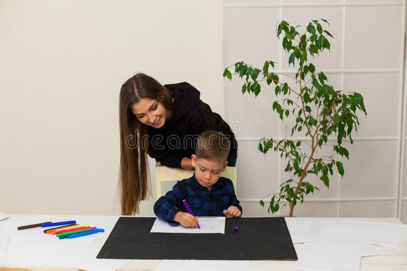 Le professeur féminin enseigne un petit garçon à dessiner à la table image libre de droits