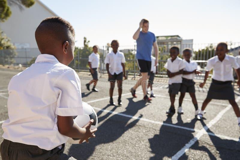 Le professeur joue au football avec des jeunes garçons dans le terrain de jeu d'école image stock