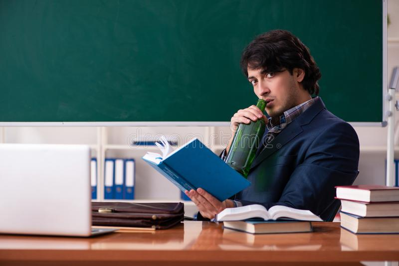 Le professeur masculin buvant dans la salle de classe images libres de droits