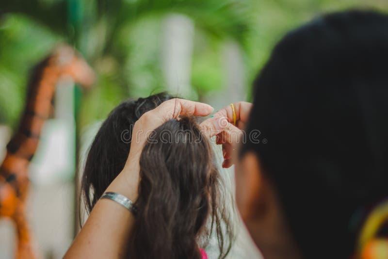 Le professeur prépare les cheveux du ` s d'étudiant avant de renvoyer la maison photos libres de droits