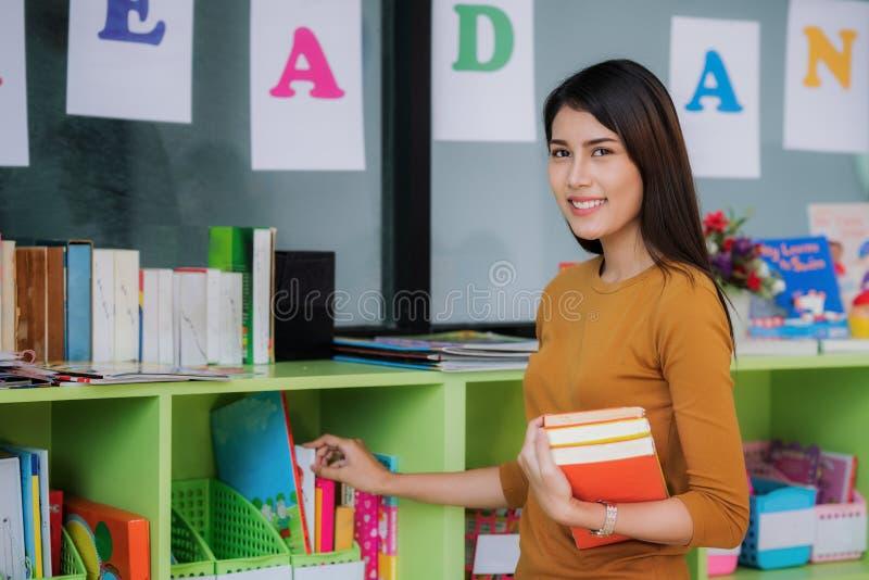 Le professeur préparent le livre pour enseignent l'étudiant dans l'école maternelle photo stock