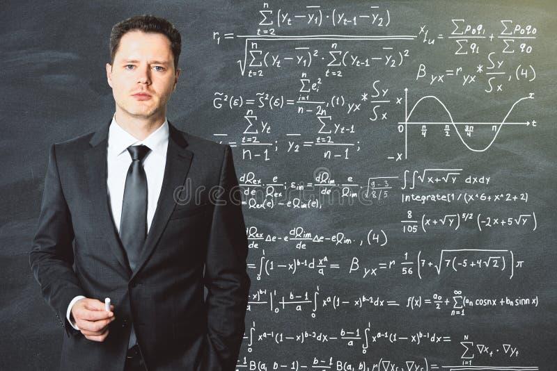 Le professeur se tient devant le tableau noir d'école sur lequel est photos stock