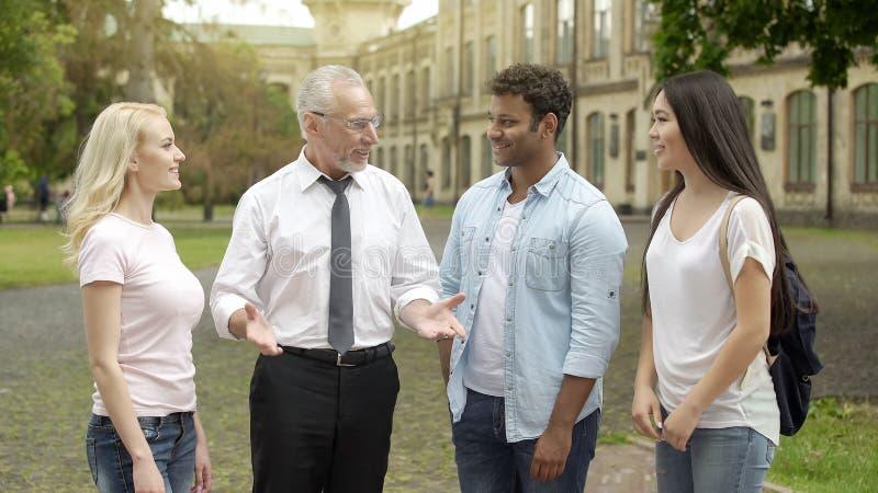 Le professeur supérieur de géographie parlant avec des étudiants s'approchent de l'université, expliquant le sujet photo stock