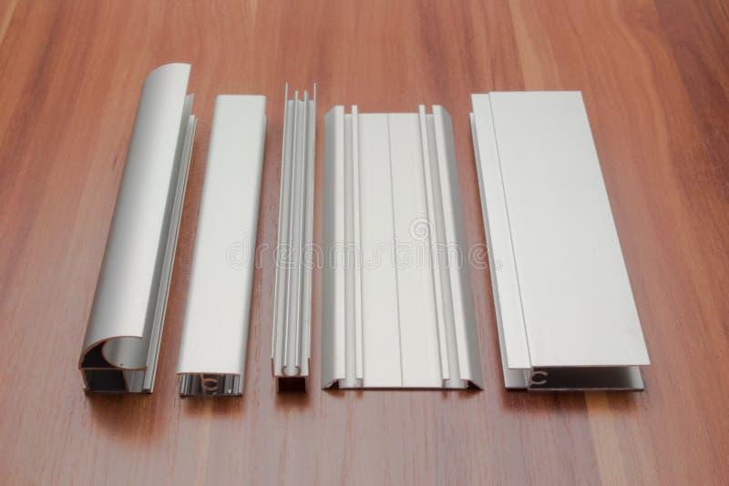 Le profil en aluminium d'une armoire coulissante est disposé sur une surface en bois photos libres de droits