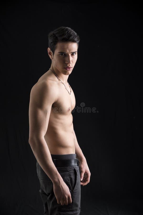 Le profil sans chemise du jeune homme musculaire beau images libres de droits