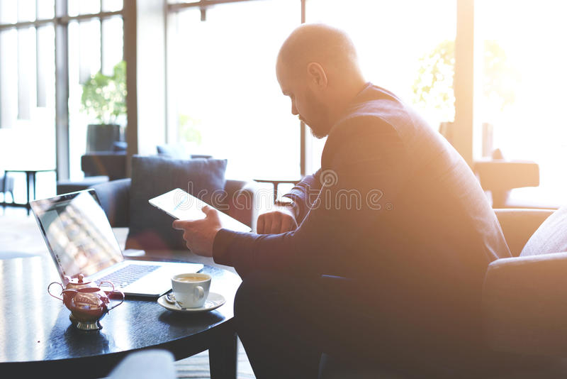 Le propriétaire de restaurant masculin avec le comprimé numérique portatif à disposition regarde sur sa montre-bracelet photos libres de droits