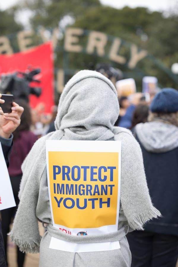 Le protestataire avec un signe qui lit protègent notre jeunesse immigrée photographie stock libre de droits