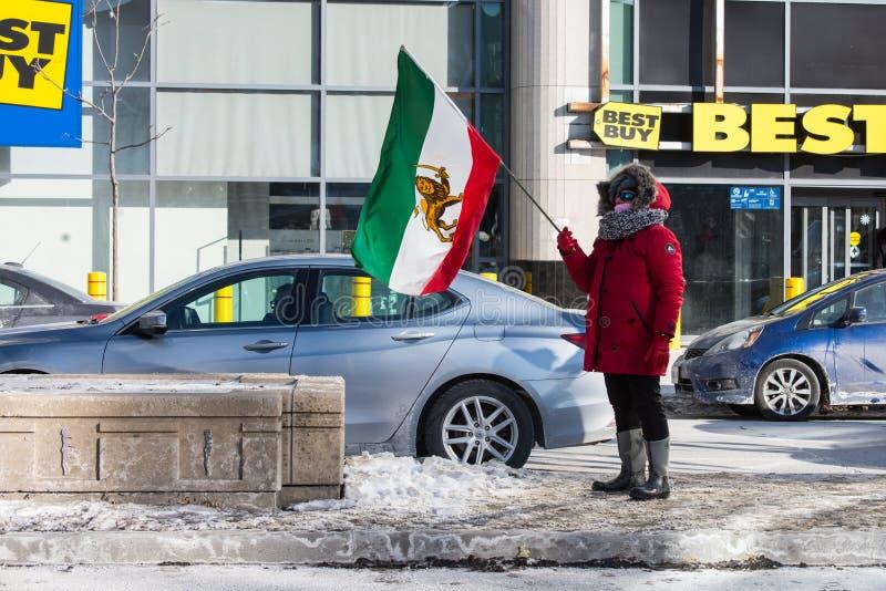 Le protestataire ondule fièrement le drapeau iranien de pré-révolution à Toronto, Canada photos stock