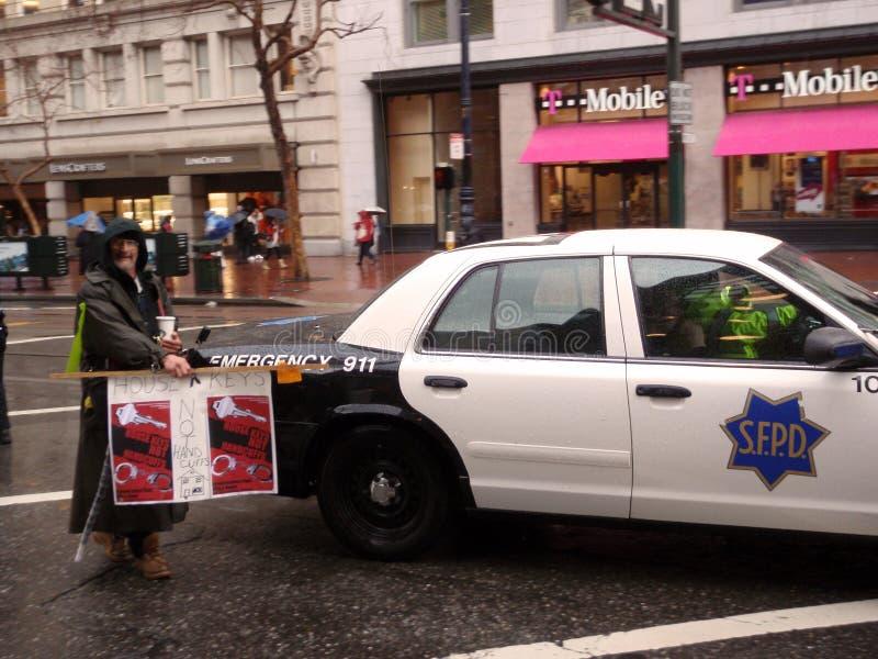 Le protestataire retient le signe devant le véhicule de SFPD photographie stock libre de droits