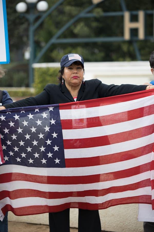 Le protestataire tient le drapeau des Etats-Unis au rassemblement de rêveurs de défense photos libres de droits