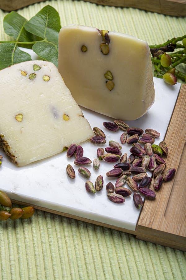 Le provolone ou le fromage italien de provola fabriqué en Sicile avec les pistaches vertes savoureuses de Bronte a servi sur la f photos libres de droits