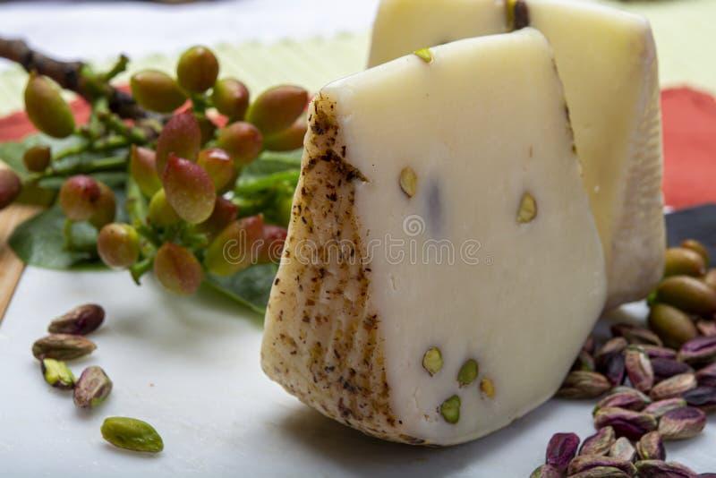 Le provolone ou le fromage italien de provola fabriqué en Sicile avec les pistaches vertes savoureuses de Bronte a servi sur la f image stock