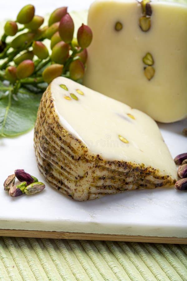 Le provolone ou le fromage italien de provola fabriqué en Sicile avec les pistaches vertes savoureuses de Bronte a servi sur la f photo libre de droits