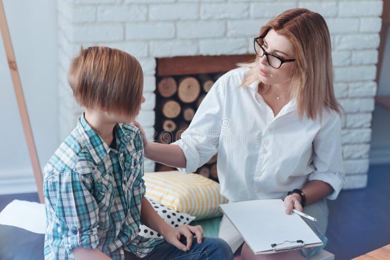 Le psychothérapeute professionnel interrogeant le patient adolescent au sujet du sien s'inquiète photo libre de droits