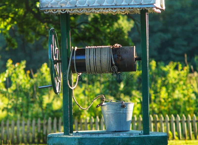 Le puits et le seau sont sur le dessus images libres de droits