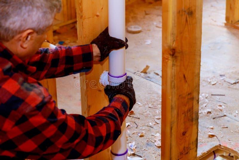 Le PVC d'Installing de plombier sifflent à en construction de la maison images stock