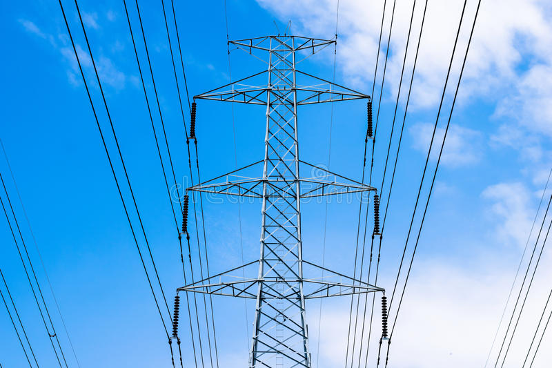 le pylône de transmission de l'électricité silhouetté contre le ciel bleu photo stock