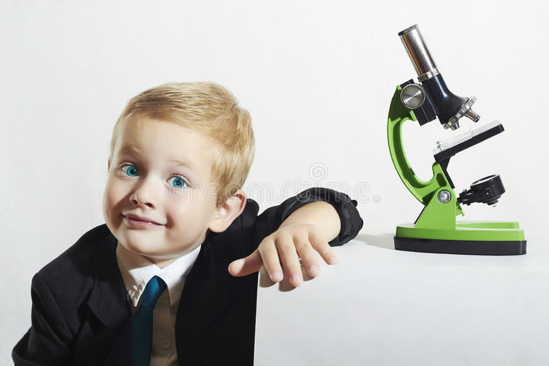 Le pysen i band roligt barn Skolpojke som arbetar med mikroskopet smart unge royaltyfri bild
