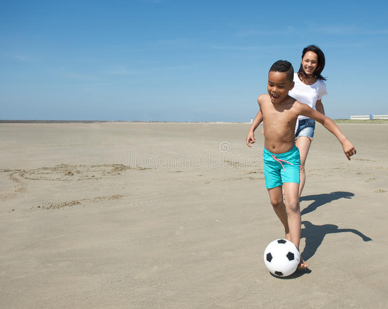 Le pysen som spelar med bollen på stranden royaltyfri bild
