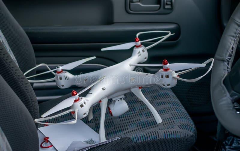 Le quadcopter se tient sur le siège de passager de voiture avec l'instruction images stock