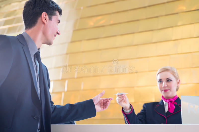 Le réceptionniste d'hôtel signent l'homme donnant la carte principale image stock