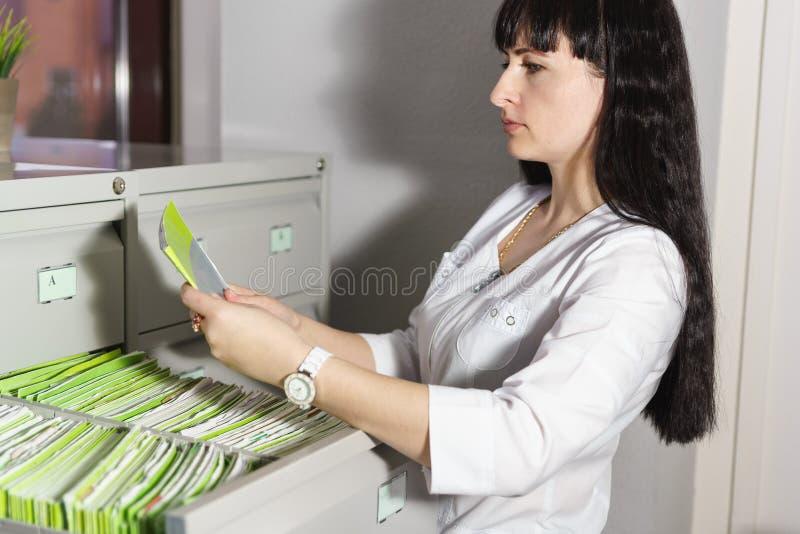 Le réceptionniste de la clinique médicale a trouvé dans le tiroir du support et lit la carte patiente désirée photographie stock
