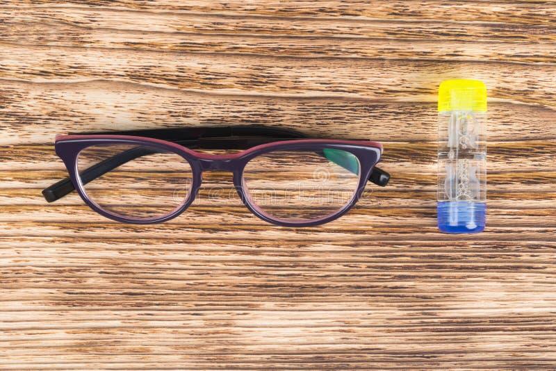Le récipient avec des verres pour la correction de la vision et les verres se trouvent sur une table en bois légère image stock
