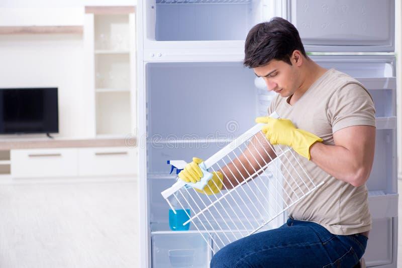 Le réfrigérateur de nettoyage d'homme dans le concept d'hygiène photographie stock