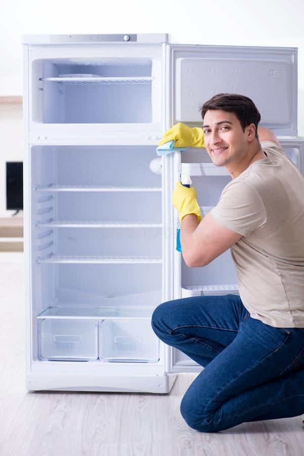 Le réfrigérateur de nettoyage d'homme dans le concept d'hygiène image stock