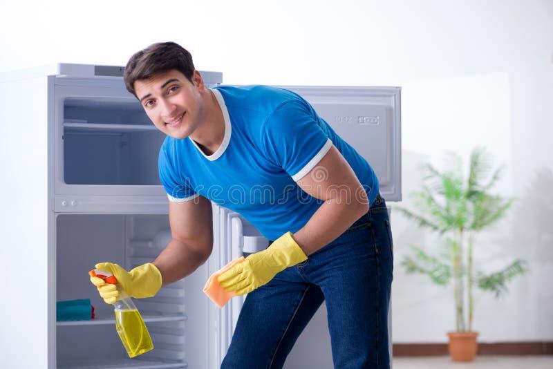 Le réfrigérateur de nettoyage d'homme dans le concept d'hygiène photo libre de droits