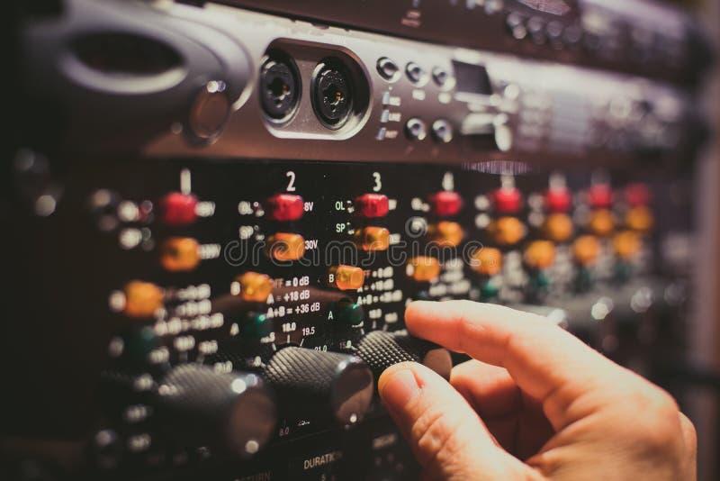 Le réglage fin humain de main nivelle sur l'équipement audio professionnel image stock