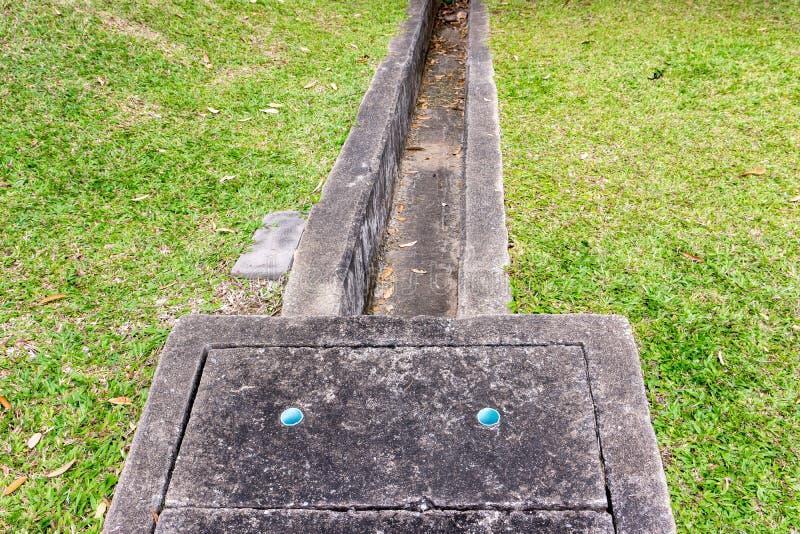 Le réservoir et la gouttière concrets de drainage près des pelouses photos libres de droits
