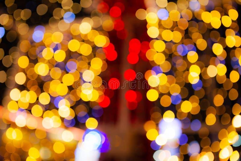 Le résumé brouillé des ampoules éclatantes rouges et d'or d'éclat allume le fond, tache floue des décorations de papier peint de  photographie stock