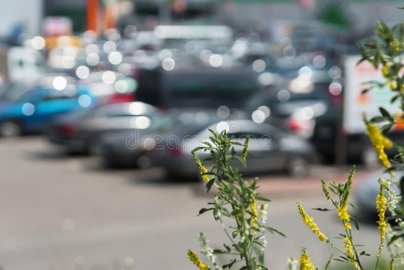 Le résumé a brouillé le stationnement extérieur à côté du centre commercial moderne, le jour d'été ensoleillé, ventes de saison,  images libres de droits